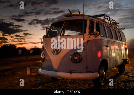 Vintage Volkswagon VW Microbus with rooftop rack for surfboards, parked along cliffs at Sunset Cliffs, San Diego, CA, USA - Stock Image