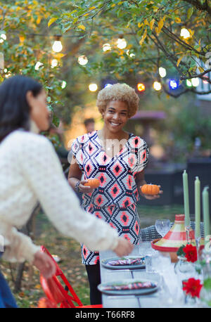 Happy women friends setting table for dinner garden party - Stock Image