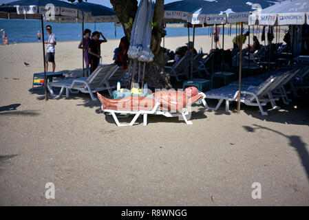 Man sunbathing on a lounger or recliner chair at the beach in Pattaya, Thailand, Southeast Asia - Stock Image