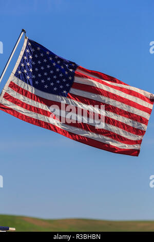 American flag flying against a blue sky - Stock Image