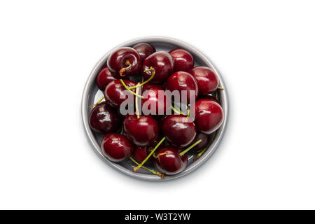 Top view of fresh Red cherries in a bowl isolated on white background. Healthy food - Stock Image