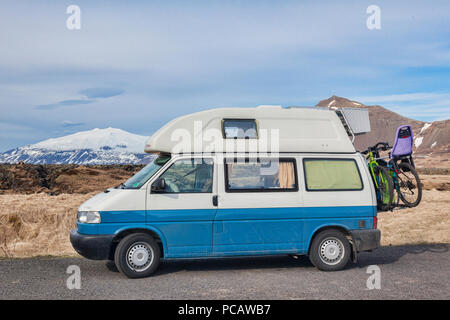 16 April 2018: Budir, Snaefellsnes Peninsula, West Iceland - Volkswagen T4 Campervan with bikes on the back, and the Snæfellsjokull Volcano in the bac - Stock Image