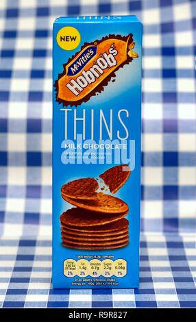 Mcvities milk chocolate thins retail pack on a blue gingham background - Stock Image