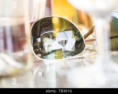 Reflection of two wineglasses in sunglasses placed on a table in a winery garden in Portugal. - Stock Image