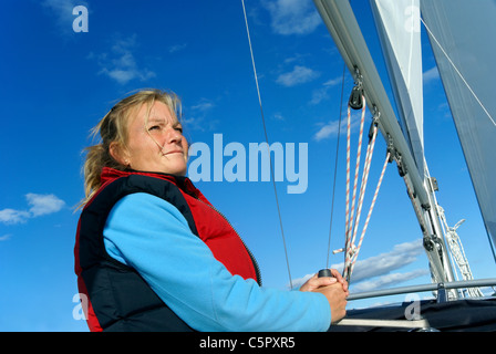 Blond woman sailing yacht (Model Release) - Stock Image