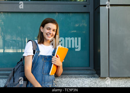 Portrait of a happy student girl leaning against the window of the school - Stock Image