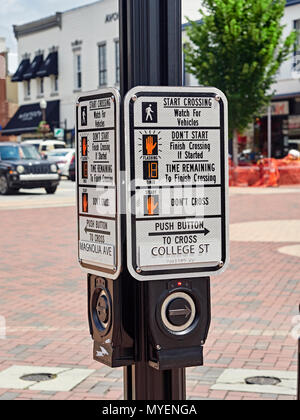 Pedestrian control or assist box and sign at a busy pedestrian crossing or crosswalk with button to help with stopping traffic in Auburn Alabama USA. - Stock Image
