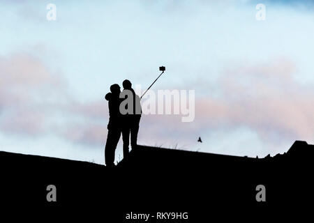 The silhouette of two people posing for a photograph using a selfie stick. - Stock Image
