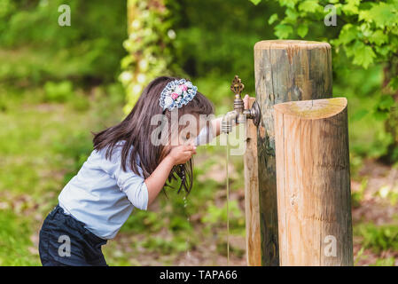 Adorable four years old cute little girl drinks water from a wooden tap in forest at a sunny day - Stock Image