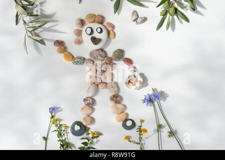 natural art, craft, picture of person surfing, made from pebbles, shells, leaves and flowers. - Stock Image