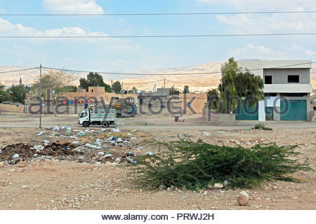 Truck Driving Through a Small Town in Jordan; Mountain Range in Background - 2018 - Stock Image