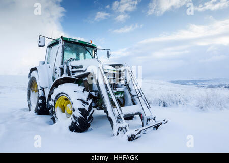 Snow covered green tractor with yellow wheel hubs in North York Moors National Park - Stock Image