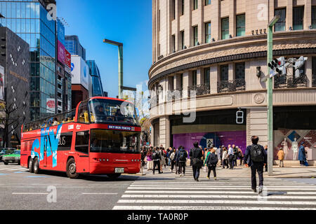 3 April 2019: Tokyo, Japan - Sky Bus Tokyo, a red open top double decker tour bus, sightseeing in the Ginza districtm stopped at a road crossing. - Stock Image