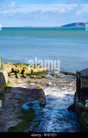 Coastal foortpath beside stream with Great Orme in distance across the Bay. Benllech, Isle of Anglesey, North Wales, UK, Britain - Stock Image