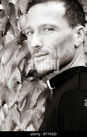 Handsome priest looks over his shoulder at camera with virginia creeper ivy in background - Stock Image