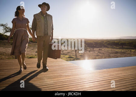 Couple walking together on wooden plank - Stock Image