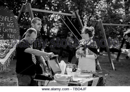 Two men preparing snacks behind a food stand at a - Stock Image
