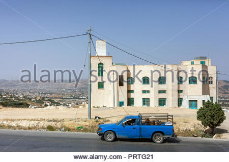 Blue vehicle driving with livestock in Jordan - Stock Image