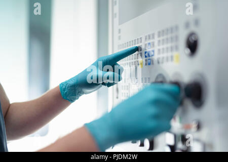 Close up of hands of apprentice engineer at controls of CNC machine in gearbox factory - Stock Image
