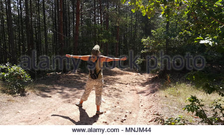 Woman in sportswear enjoying the nature on a forest road in the mountain - Stock Image