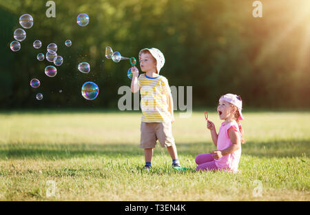 Happy children having fun in grass on sunny summer evening - Stock Image
