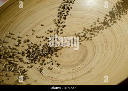 Closeup of hemp seeds tumbling ito a bamboo bowl - Stock Image