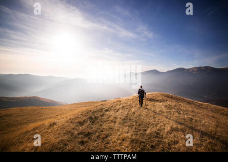 Rear view of male backpacker walking on mountain against sky - Stock Image