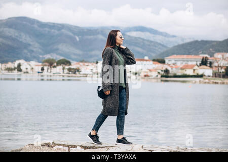 Beautiful young trendy girl walks near the sea against the backdrop of Tivat in Montenegro. - Stock Image