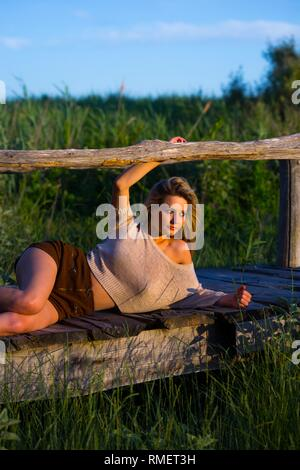 Attractive mesmerizing young woman in nature in sunset evening time lying sideways looking away at setting sun - Stock Image