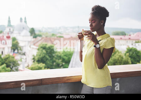 Beautiful young African American business woman drinking coffee at a cafe. Beautiful cozy place - Stock Image