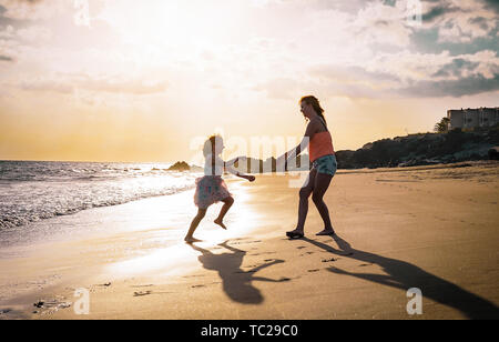 Mother and daughter playing on the beach at sunset - Happy family having fun in vacation on the beach - Parenthood, happiness and love concept - Stock Image