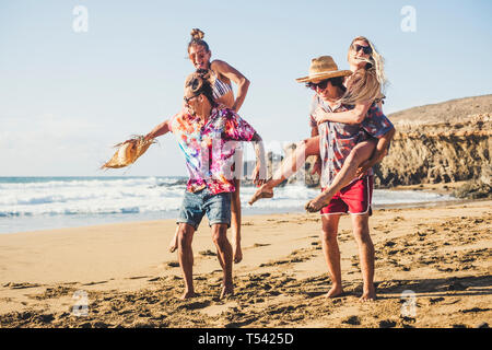 Happy group of people on vaation - youthful and funny concept with young men and women having fun together in friendship playing - boys carrying girls - Stock Image