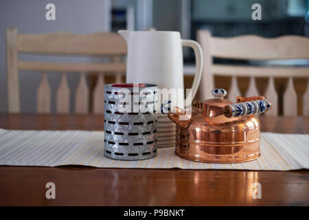 A decorative grouping of a pitcher, a copper kettle, and a zinc metal candle holder on a dining room table with runner. USA. - Stock Image