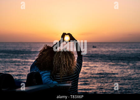 Romantic friendship people concept with two curly lady viewed from back doing hearth love sign with hands to celebrate the summer holiday vacation tra - Stock Image