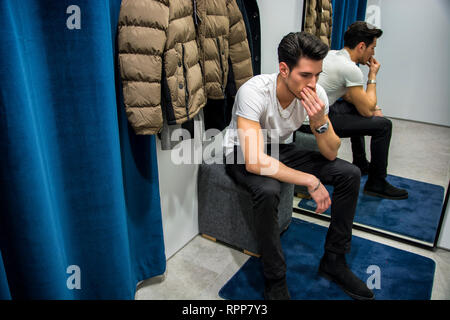 Young Man Trying on Clothes in Clothing Store - Stock Image