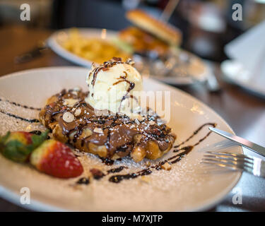 Hot Waffle and Ice Cream and Chocolate Sauce - Stock Image