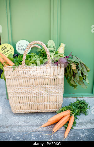 Bag full of healthy raw vegetables from local market with stickers on the green background - Stock Image