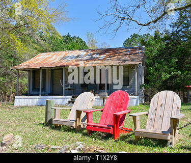Small cabin in rural Alabama with three wooden chairs in the front yard showing country living or lifestyle in the South. - Stock Image
