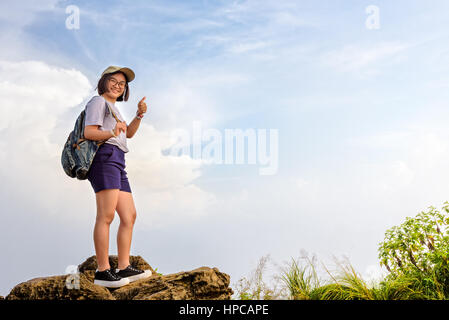 Happy hiker asian cute teens girl with backpack cap and glasses standing smiling poses thumb up on mountain and - Stock Image