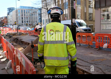 Worker wearing London Highways Alliance logo on back of jacket working on Cycle Superhighway cycling lane on Clerkenwell Road London UK  KATHY DEWITT - Stock Image