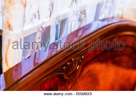 Close up of a wooden luxury bed and white curtains by a window in a room. - Stock Image