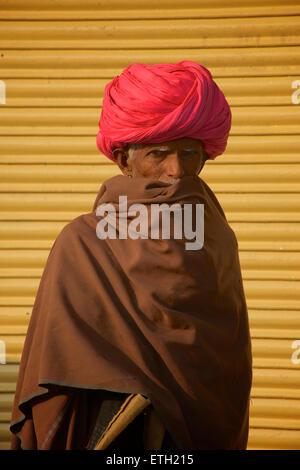 Indian man in pink turban against yellow shutters, Jodhpur, Rajasthan, India - Stock Image