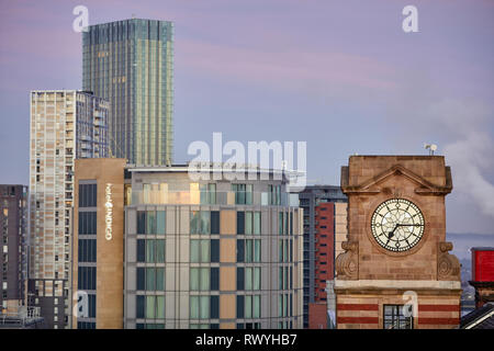 Dawn first light Manchester a old clock on a coop building with salford behind - Stock Image