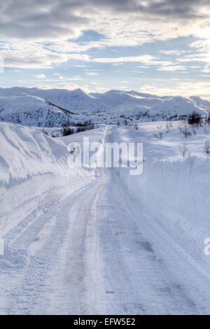 Picture of a road covered with snow, with mountains in the back - Stock Image