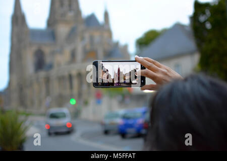 A tourist captures a photo with her cell phone of the gothic Bayeux Cathedral in Bayeux France, Normandy. - Stock Image