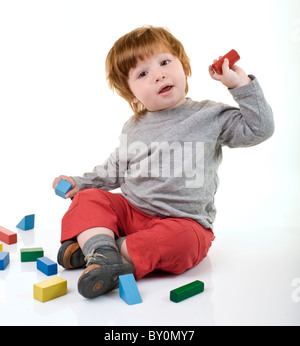 red head boy playing with building blocks - Stock Image