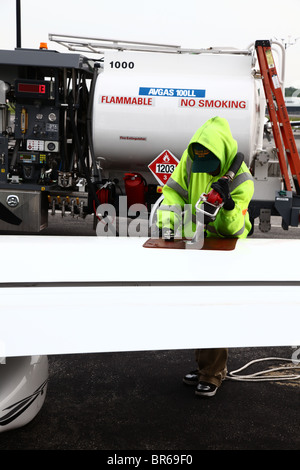 Man fueling up a Cirrus SR22 airplane at Westchester County Airport, Harrison, NY, USA - Stock Image