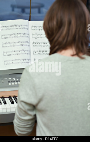 rear view of young woman playing keyboard - Stock Image