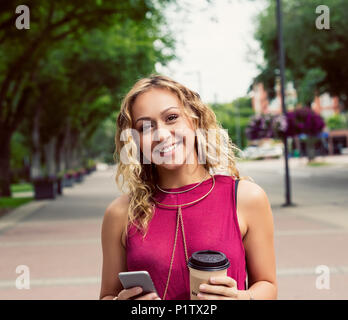A young woman looks at the camera while walking down a street with a coffee near a university campus and texting on her smart phone - Stock Image