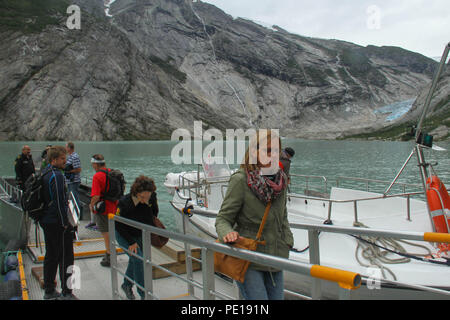 Nigardsbreeen, Norway - 7 August 2018: Tourist disembark from a boat trip to the bottom of the Nigardsbreeen Glacier. The glacier is about an hours drive from Skjolden. Photo: David Mbiyu - Stock Image